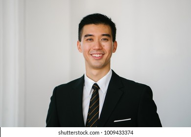 Portrait head shot of a handsome, confident and young Asian man smiling at the camera. He is in a dark suit, white shirt, professional tie and pocket square.
