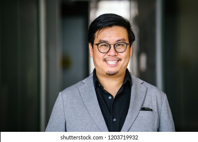Portrait head shot of a middle-aged Chinese Asian (Singaporean) man dressed in smart casual (black shirt, light grey suit) and spectacles. He is smiling as he looks at the camera for his head shot.
