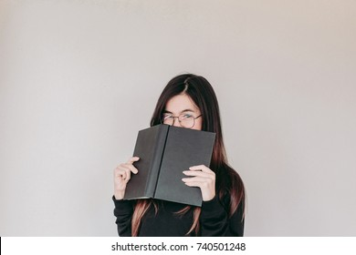 portrait head shot of Young asian Student woman wearing glasses holding book with copy space
