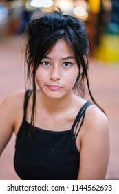 Portrait head shot of a young, attractive Chinese Asian skater girl. She is a teenager and millennial and is dressed in sporty attire and has long hair. The girl is sitting at a food court.