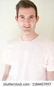 Portrait headshot a white man in a t-shirt against a white background smiling looking at camera. Fit and healthy man posing for the camera. Happy man smiling.