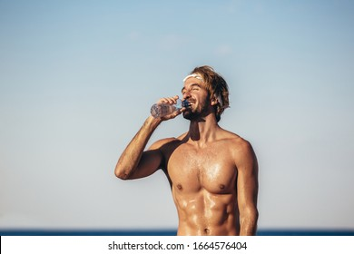 Portrait of healthy athletic man with fit body holding bottle of refreshing water, resting after workout or running at beach.