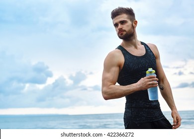 Portrait Of Healthy Athletic Man With Fit Body Holding Bottle Of Refreshing Water, Resting After Workout Or Running At Beach. Thirsty Male With A Drink After Outdoor Training. Sports, Fitness Concept