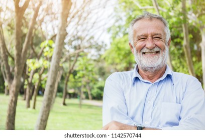 Portrait of healthy happy smile senior elderly caucasian old man grandfather in the park outdoors with copy space. Spring autumn golden age healthcare cheerful lifestyle freedom retirement concept