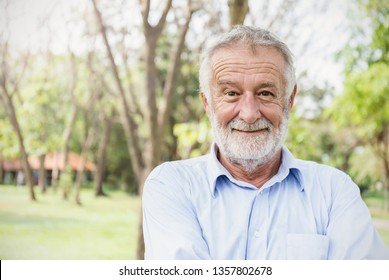 Portrait of healthy happy smile senior elderly caucasian old man in the park outdoors with copy space. Spring autumn golden age healthcare cheerful lifestyle freedom retirement concept