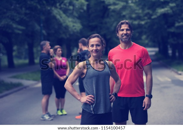portrait of a healthy jogging couple with the rest of their running team in the background