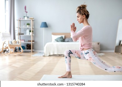 Portrait of healthy lady going yoga workout in room. Fitness woman exercising at home.