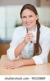 Portrait of a healthy woman drinking milk in her kitchen