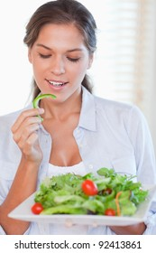 Portrait of a healthy woman eating a salad in her kitchen
