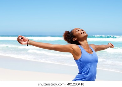 Portrait of healthy young african woman standing on the beach with her hands outstretched