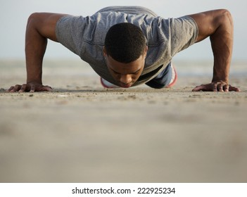 Portrait of a healthy young man doing push ups at the beach