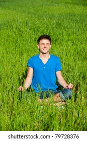 portrait of healthy young man meditation on green grass