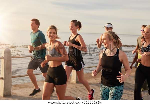 Portrait of healthy young men and women running together on seaside promenade. Active running club group training outdoors by the sea.