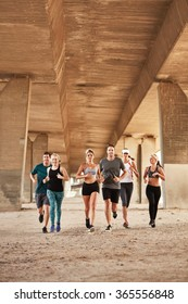 Portrait of healthy young people running under a bridge. Running club group wearing sport clothing training in the city.