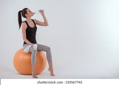 Portrait of healthy young sportswoman after doing exercises   sitting  on  orange exercise  ball  with towel drinking  bottle of mineral water isolated on white background full length