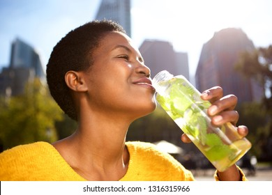 Portrait of healthy young woman drinking water outdoors