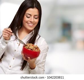 portrait of healthy young woman eating cereals indoor