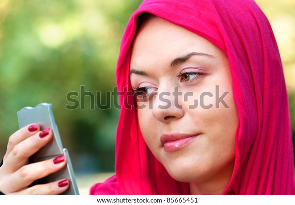 Portrait of healthy young woman wearing red scarf and looking in a mirror for  wrinkles