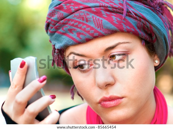Portrait of healthy young woman wearing colorful scarf and looking in a mirror for wrinkles