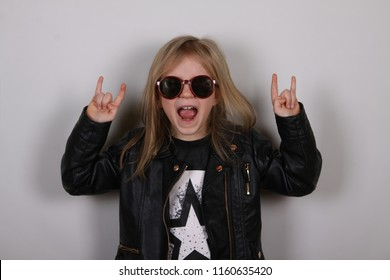 Portrait of a heavy metal little girl with sunglasses. Cute little girl making a rock-n-roll sign