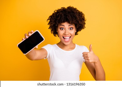 Portrait of her she nice attractive charming cheerful cheery ecstatic wavy-haired lady holding in hands cell showing giving black screen thumbup isolated on bright vivid shine yellow background