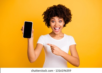 Portrait of her she nice attractive lovely charming cheerful cheery ecstatic wavy-haired lady holding in hands cell showing black screen isolated on bright vivid shine yellow background
