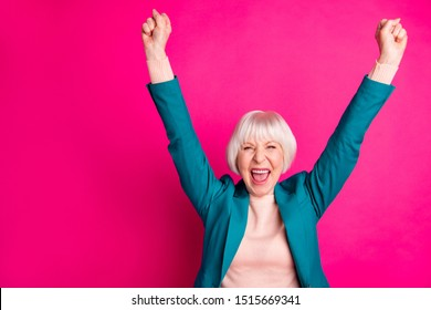 Portrait of her she nice attractive cheerful cheery overjoyed gray-haired lady wearing blue green jacket rejoicing rising hands up isolated on bright vivid shine vibrant pink fuchsia color background