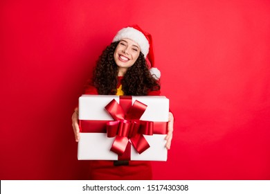 Portrait of her she nice attractive lovely charming cheerful cheery glad generous wavy-haired Santa girl giving bow ribbon box isolated on bright vivid shine vibrant red color background