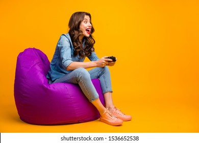 Portrait of her she nice attractive lovely cheerful cheery glad addicted wavy-haired girl sitting on bag chair playing video game device isolated on bright vivid shine vibrant yellow color background