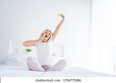 Portrait of her she nice attractive lovely pretty dreamy sleepy senior woman sitting in bed stretching yawning waking up in modern light white interior room flat apartment hotel indoors