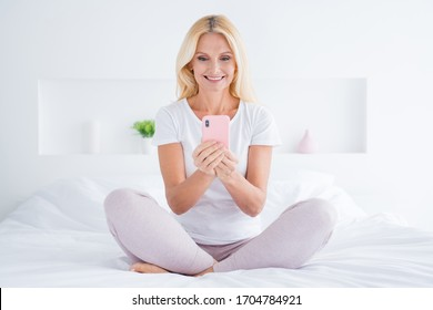 Portrait of her she nice attractive lovely pretty shine cheerful focused senior woman sitting in bed using digital device quarantine stay home in modern light white interior room flat apartment