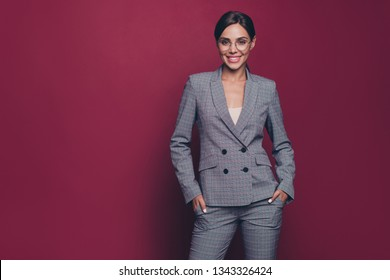 Portrait of her she nice classy pretty representative attractive cool cheerful cheery lady financier director wearing gray checkered suit isolated over maroon burgundy marsala pastel background