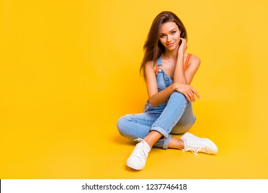 Portrait of her she nice cute winsome attractive charming cheerful positive lady wearing jeans denim overall sitting on floor isolated over bright vivid shine yellow background
