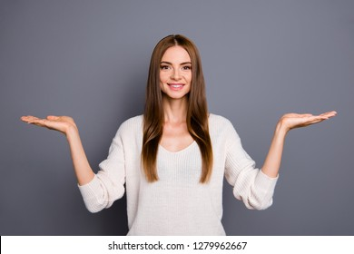 Portrait of her she nice cute lovely sweet lovable attractive charming cheerful straight-haired lady showing two object on palm copy empty blank space place isolated over gray pastel background