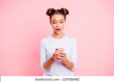 Portrait of her she nice cute lovable fascinating attractive lovely sweet cheerful amazed glad girl holding cell in hands reading sms isolated over pastel pink background