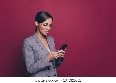 Portrait of her she nice cute attractive lovely sweet winsome classy gorgeous focused concentrated lady wearing gray checkered jacket using new device isolated over maroon burgundy marsala background