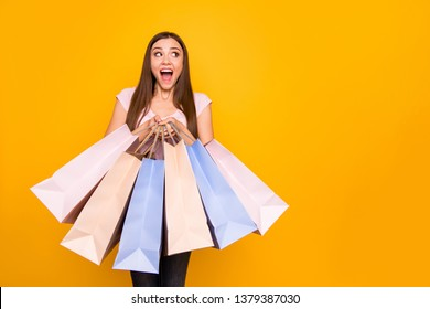 Portrait of her she nice cute charming lovely winsome attractive cheerful cheery straight-haired girl holding in hands new bags purchase win winner isolated on bright vivid shine yellow background