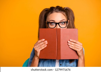 Portrait of her she nice foxy lovely attractive cheerful positive school girl holding in hands hiding behind opened book exam preparation isolated over bright vivid shine yellow background