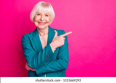Portrait of her she nice-looking attractive lovely cheerful cheery glad gray-haired lady pointing forefinger aside ad new novelty isolated over bright vivid shine vibrant pink fuchsia color background