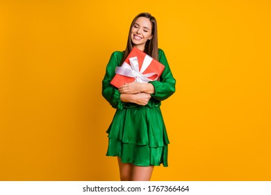 Portrait of her she nice-looking attractive lovely dreamy cheerful straight-haired girl holding in hand embracing giftbox isolated over bright vivid shine vibrant yellow color background