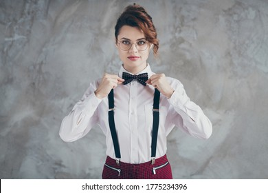 Portrait of her she nice-looking attractive lovely pretty serious classy elegant wavy-haired girl fixing bowtie wear isolated over gray concrete industrial wall background