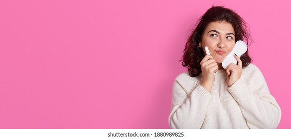 Portrait of hesitant young woman holds two intimate products, chooses between tampon and pad during menses, thinks what gives better protection, poses against pink wall, copy space for advertisement