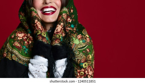 Portrait of High fashion glamour beautiful brunette hair Russian style woman in traditional scarf and gloves on red background