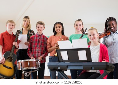 Portrait Of High School Students Playing In School Orchestra With Teacher