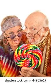 Portrait of hippie seniors licking a large lollipop