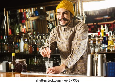 Portrait of hipster barman mixing a cocktail with a spoon at bar background.