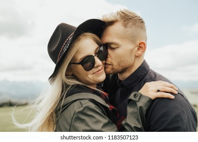 Portrait of hipster couple on the top of mountains enjoying mountains and clouds landscape. Love and travel concept. Lifestyle concept. family active traveling. Mountain view