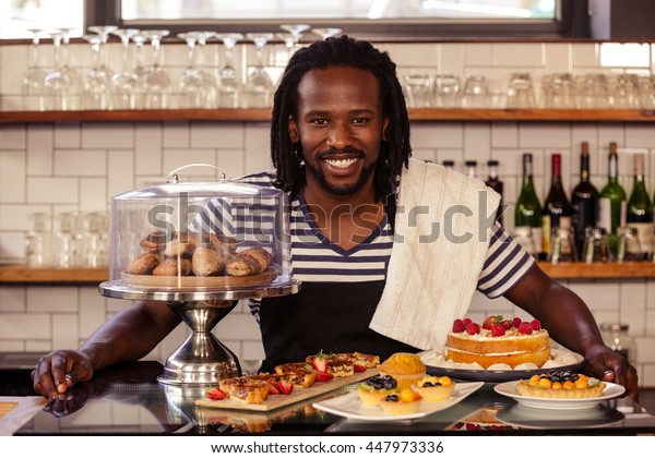Portrait of hipster employee posing with pastries at cafe