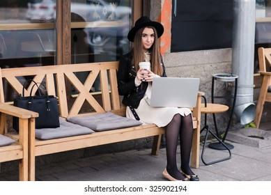 Portrait of a hipster girl dressed in stylish clothes posing while sitting with net-book on a cozy bench in sidewalk cafe,young beautiful female enjoying coffee during work on portable laptop computer