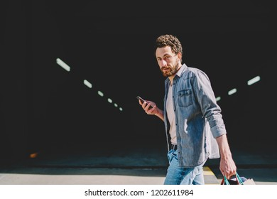 Portrait of hipster guy customer dressed in casual wear holding paper bags after shopping in modern mall and updating profile in network on smartphone device strolling near parking lot